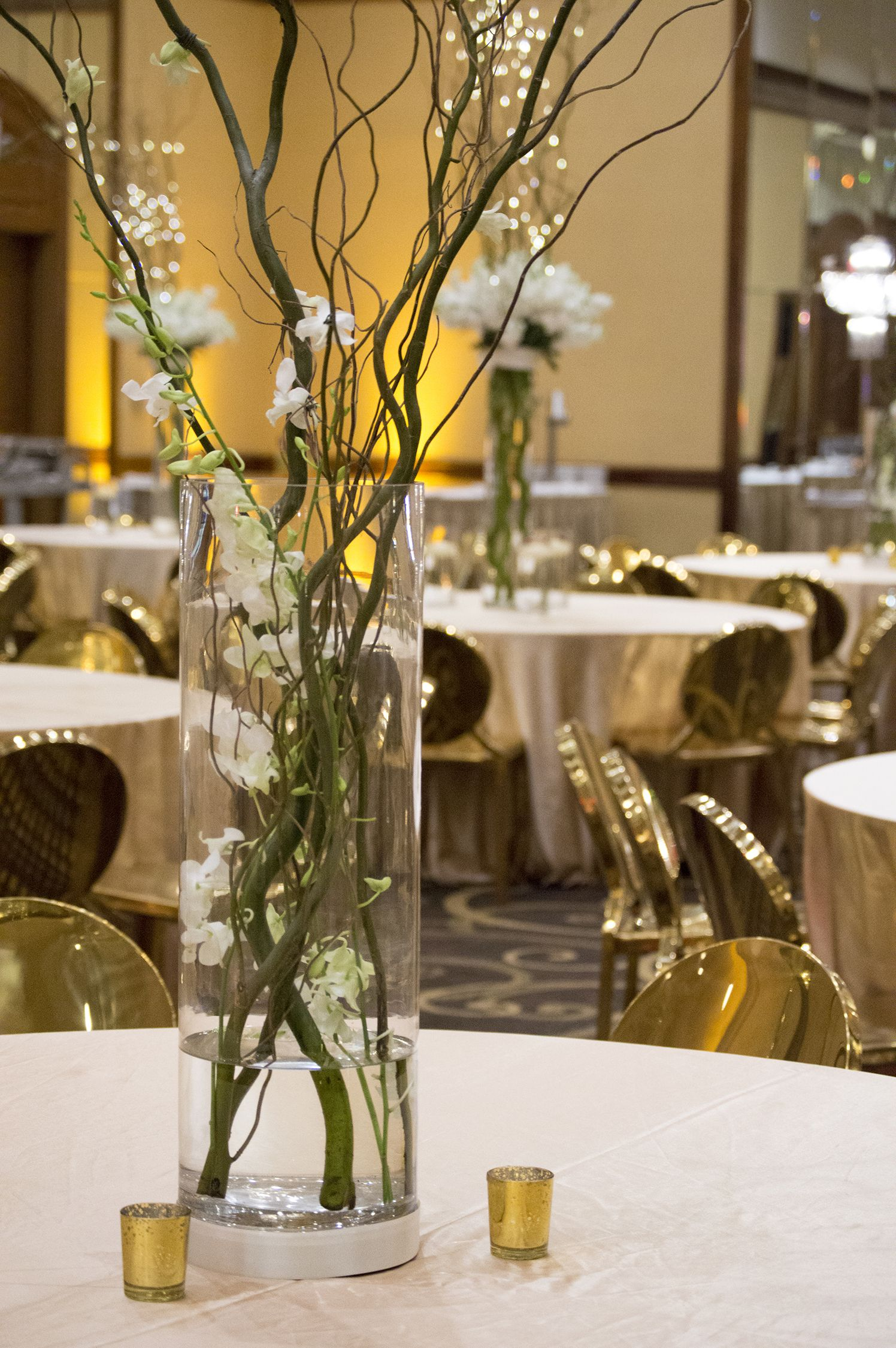 Gold Wedding Featuring Curly Willow And Dendrobium Orchid Centerpieces Rent These Gold Chairs For Y Dendrobium Orchids Centerpiece Orchids Orchid Centerpieces