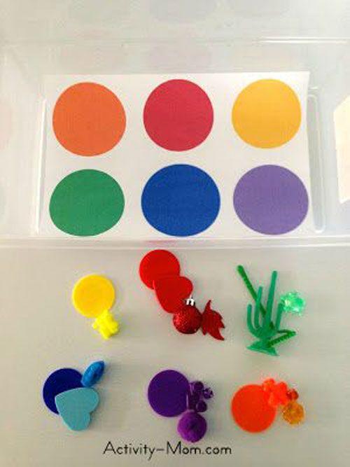 Lag med f.eks. eggkartong (liten lilla? 6-pk.?) der hver fordypning har ulike farger, og en tilhørende pose med gjenstander i ulike farger.