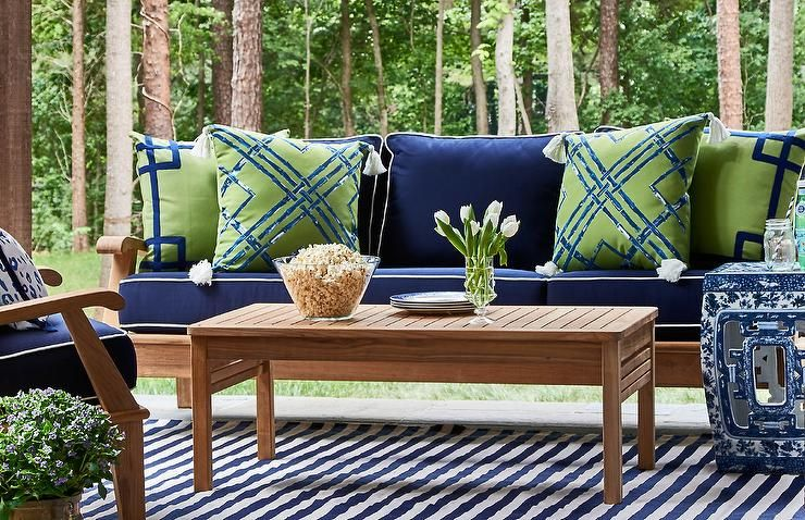 Patio Features A Teak Sofa Lined With Blue Cushions With