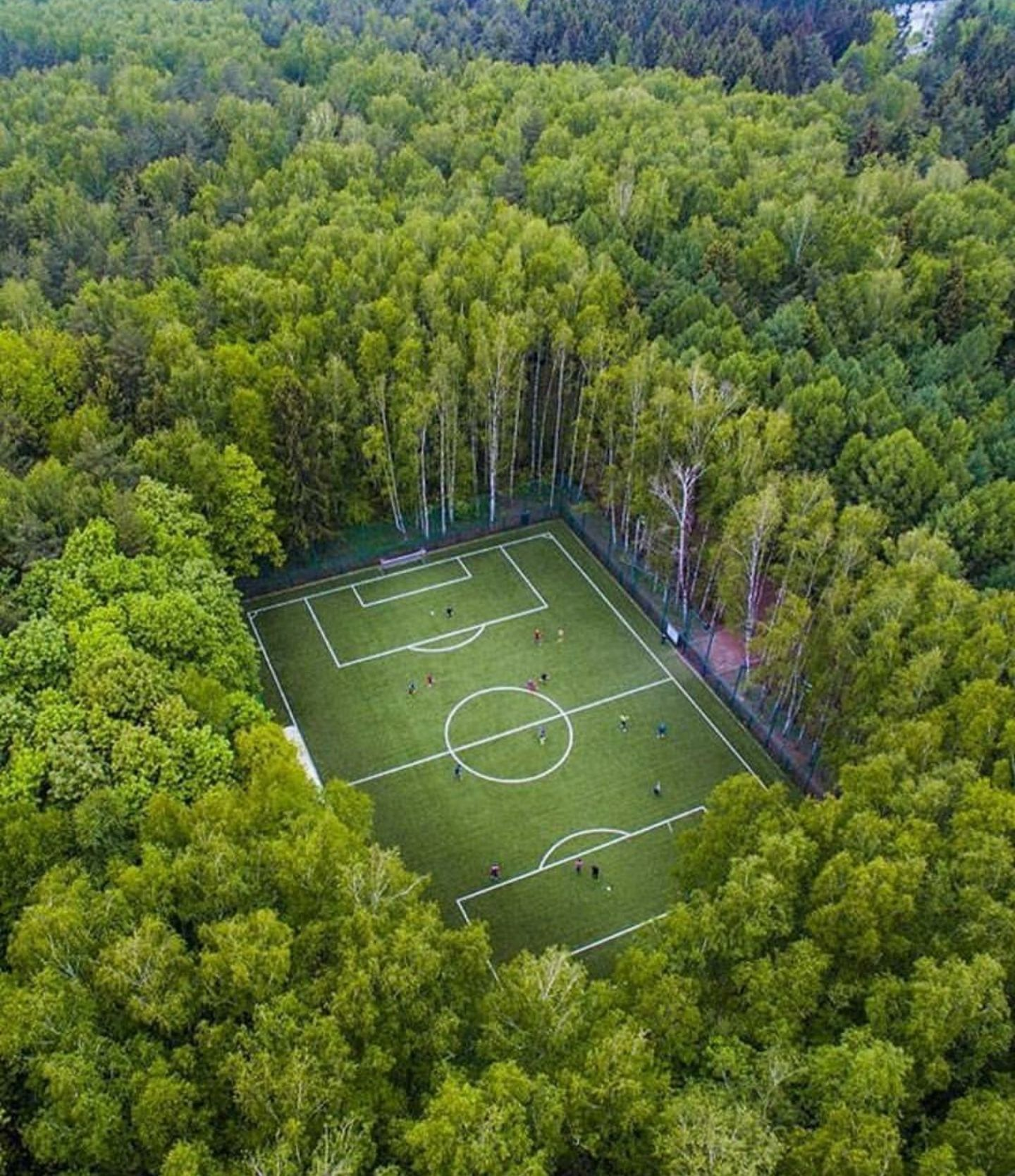drone shot of a soccer field in the middle of the woods in moscow