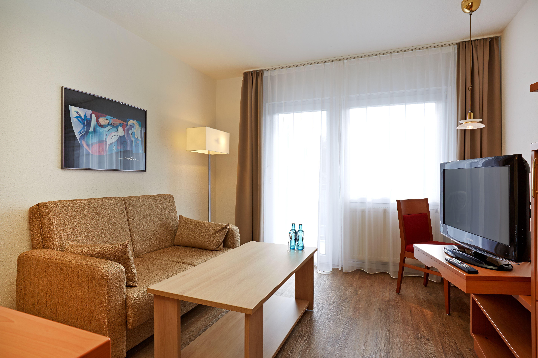 Wohnzimmer in einem der Apartments im H+ Hotel Wiesbaden Niedernhausen. Hier kann man sich nach einem anstrengenden Arbeitstag entspannen.