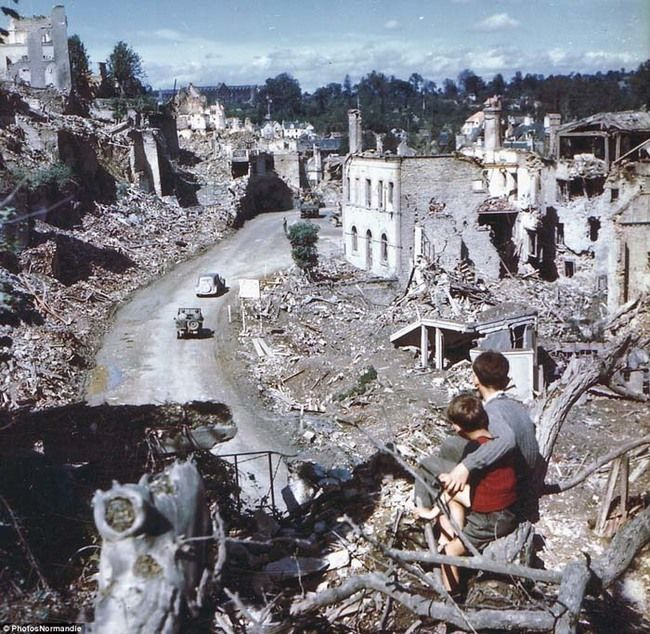 In the aftermath of the D-Day invasion, two boys watch from a hilltop as American soldiers drive through the town of St. Lo. France (1944).
