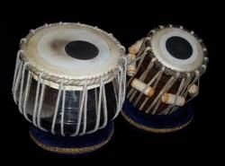 TABLA Entre los instrumentos de percusión destacar un instrumento doble llamado tabla, La tabla es uno de los instrumentos más conocidos de la India. En realidad se trata de un par de tambores: la tabla propiamente dicha, que es un pequeño tambor vertical de sonido más agudo, con un solo parche tensado con cuerdas de cuero y rodillos de madera bajo las cuerdas para modificar la tensión, y, por lo tanto, la altura de sonido. El segundo tambor, llamado bâyâ, es un pequeño timbal con forma de…