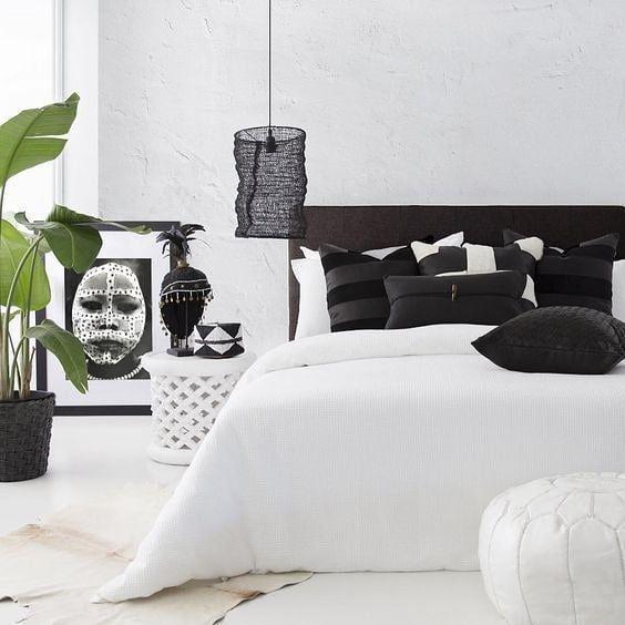 Black and white bedroom with framed Maasai portrait #pillows #jujuhat #kubacloth#designideas #designinspiration #designlovers #designersaree #designsponge #designersarees #designbuild #designersuits #fashionmuslim #scandinaviandesign #industrialdesign #nailsdesign #nailartist