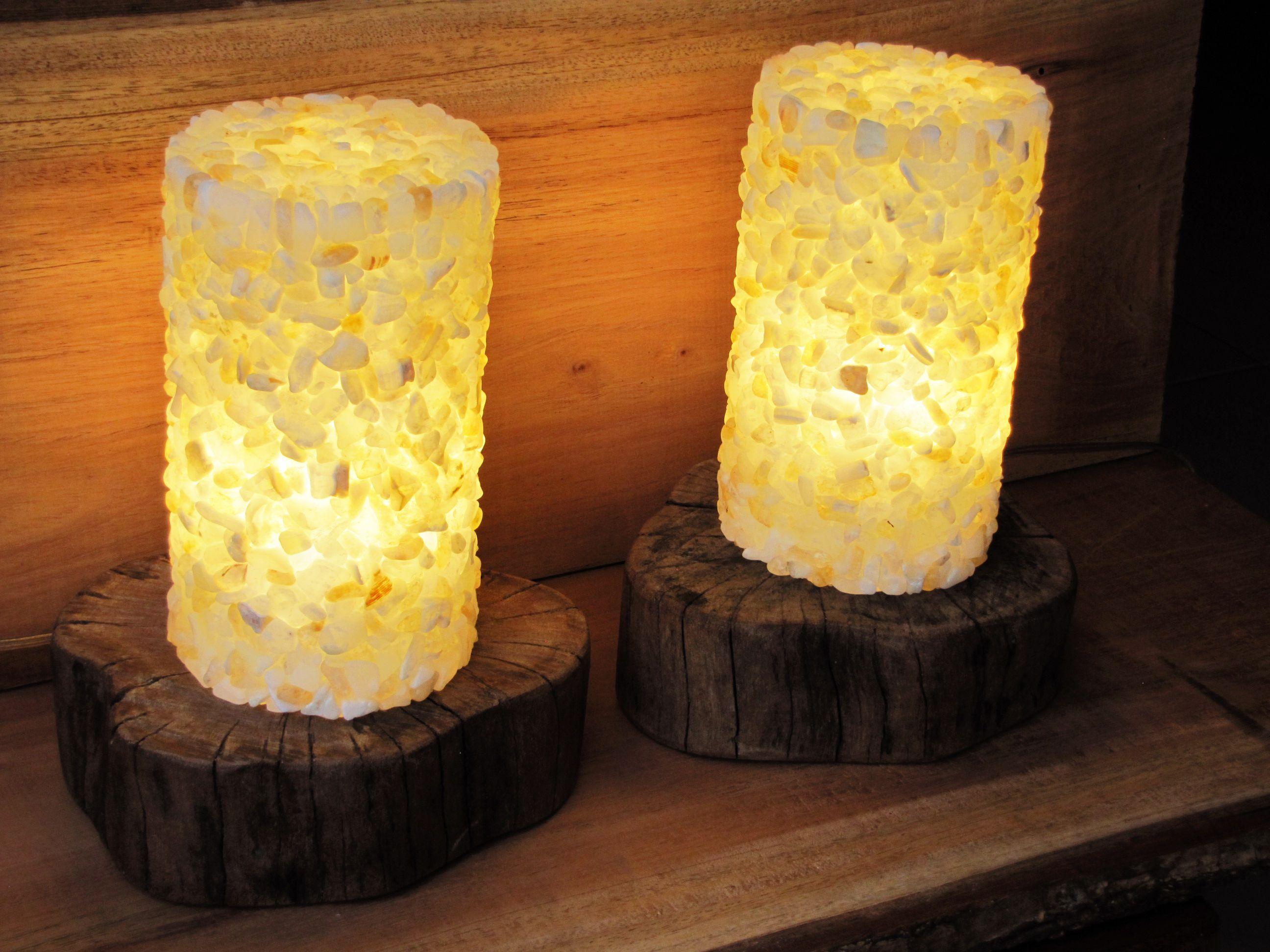 Luminárias cilíndricas que tem como base o reaproveitamento de pequenos troncos de madeira. No revestimento musivo das mesmas, foi utilizada uma harmoniosa mistura de pedras roladas (ônix e citrino). Para iluminação interna, lâmpadas do tipo LED, com menor consumo energético e baixo aquecimento.  Medidas aproximadas: 22cm (diâmetro da base) x 29cm (altura).