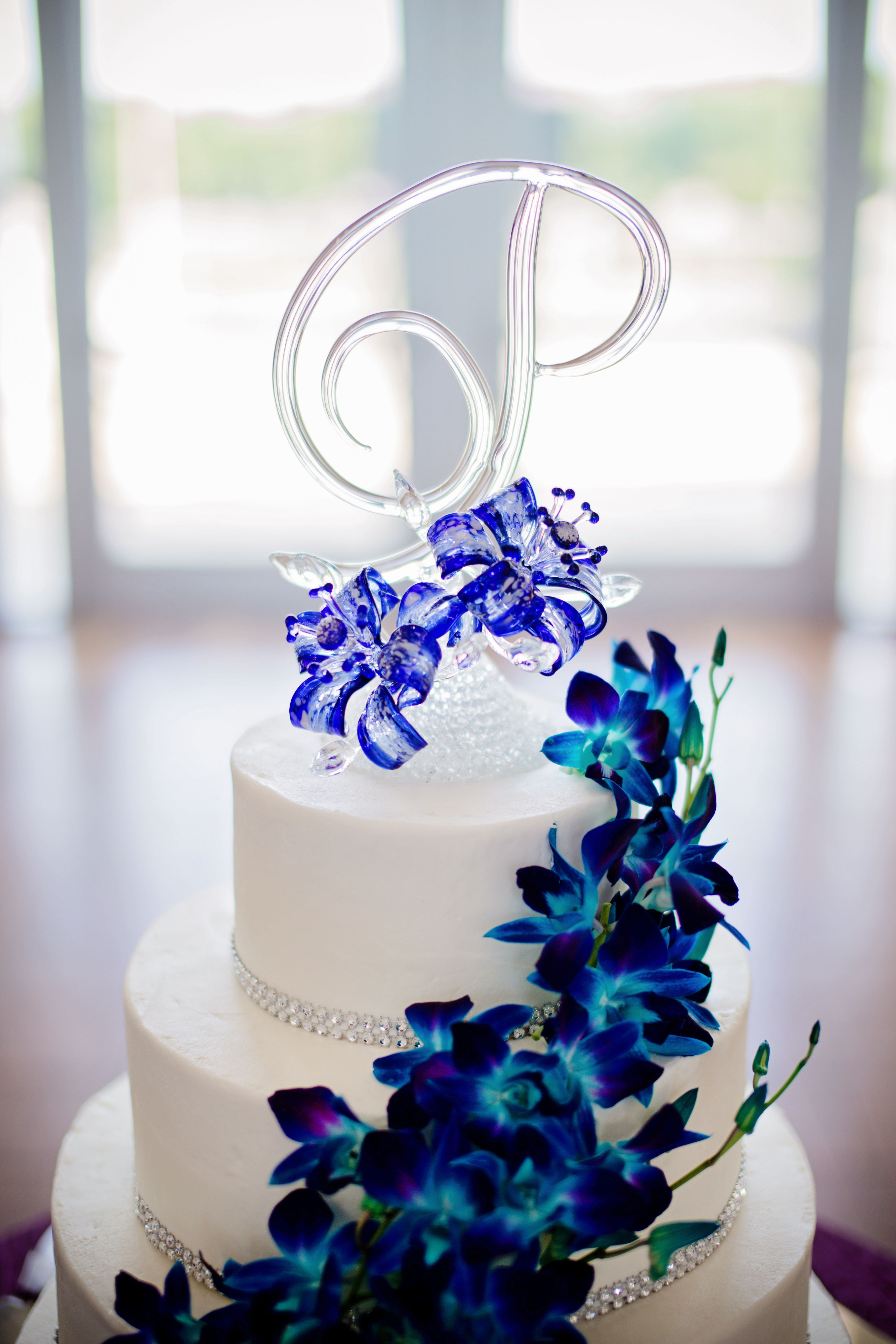 Blown glass wedding cake topper. Buttercream frosting with blue ...