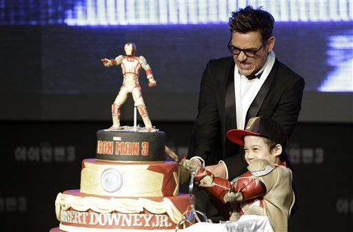 US actor Robert Downey Jr cuts his birthday cake with a boy