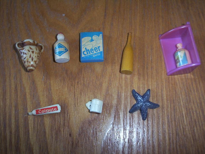There is a pink corner shelf with a bottle attached that says liquid soap on it , a tiny cup that says baby on it , a tiny tube of colgate toothpaste , tiny bottle of clorox bleach , tiny wood box of cheer , tiny yellow bottle , starfish , and what looks like a two handle vase