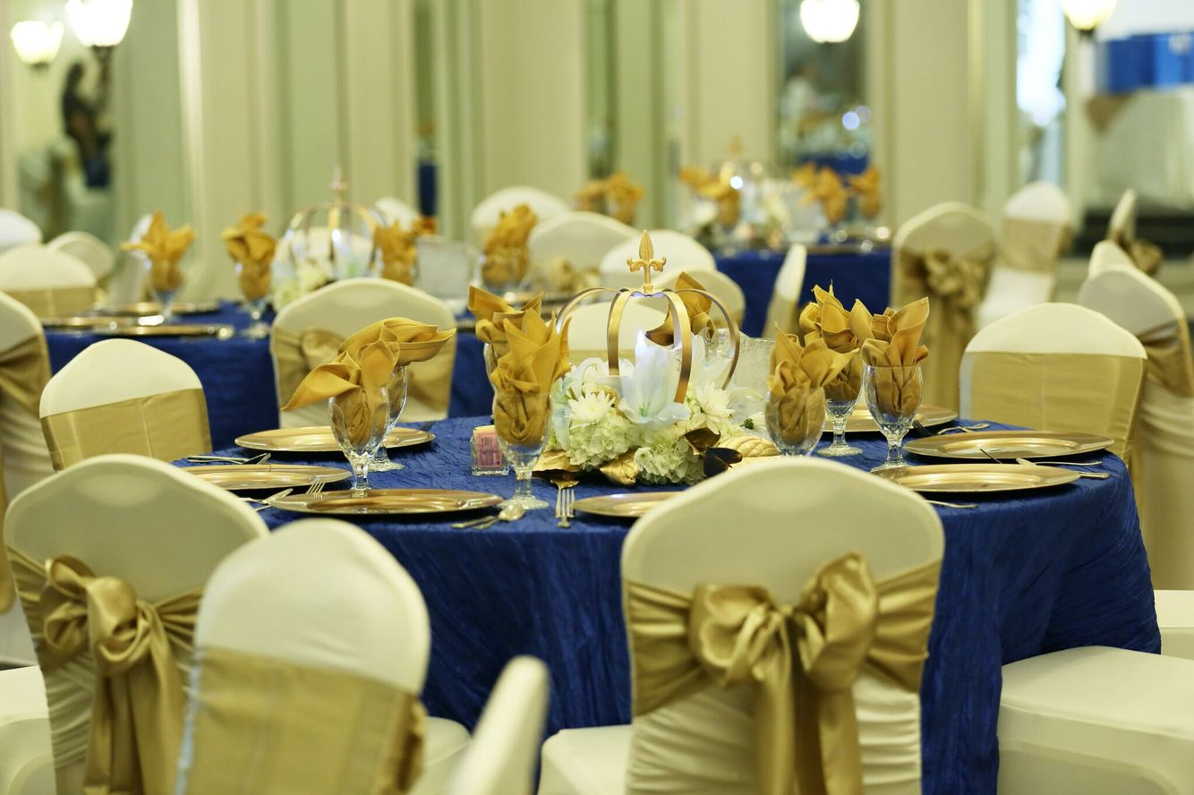 White fitted chair covers with gold bow, royal blue and