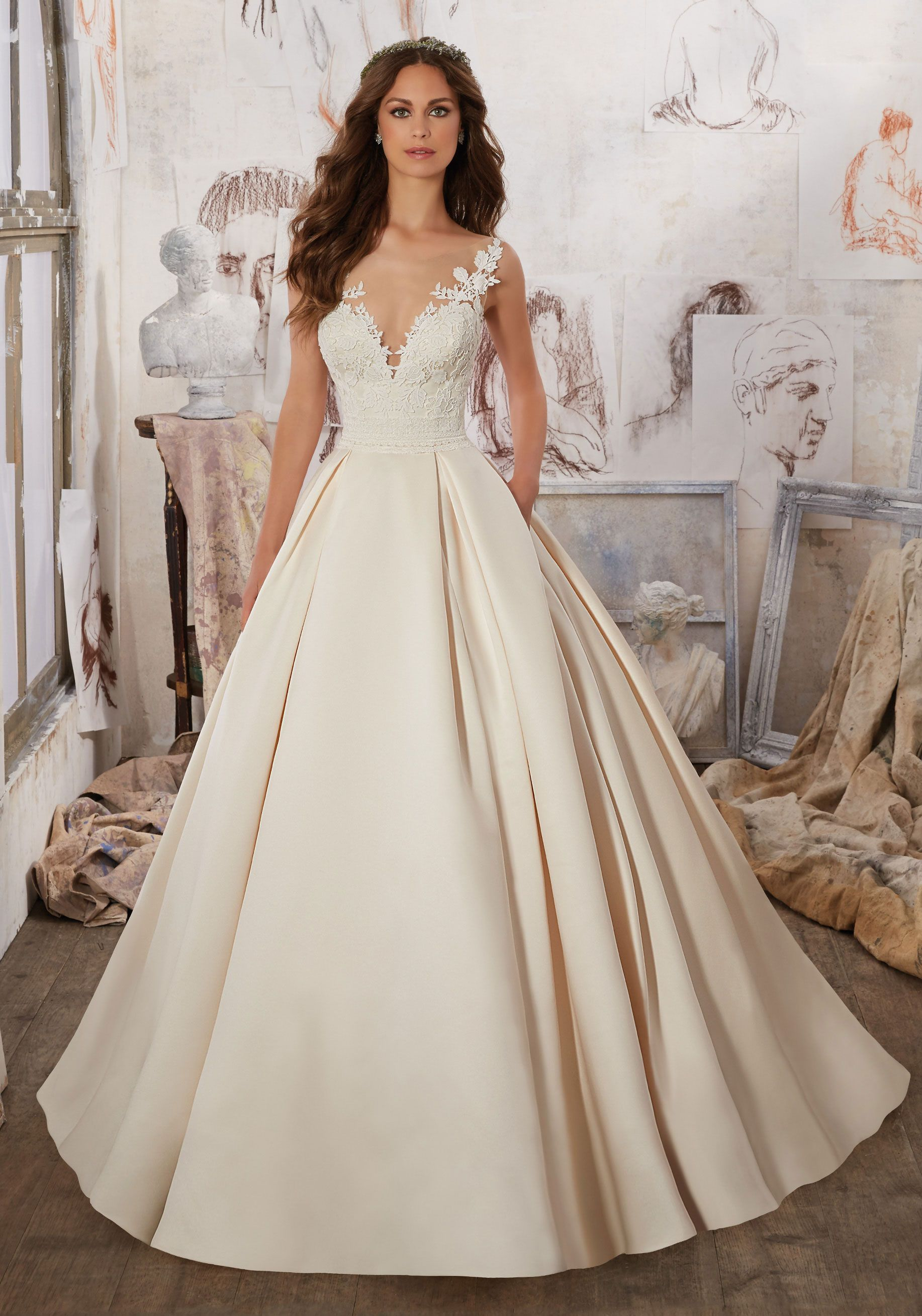 Exquisite guipure lace appliquéŽs and trim adorn the bodice and