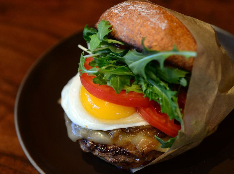 A Sunny Side burger from  Roam Artisan Burger Free-Range egg, aged white cheddar, caramelized onions, greens, tomato, sweet chili sauce