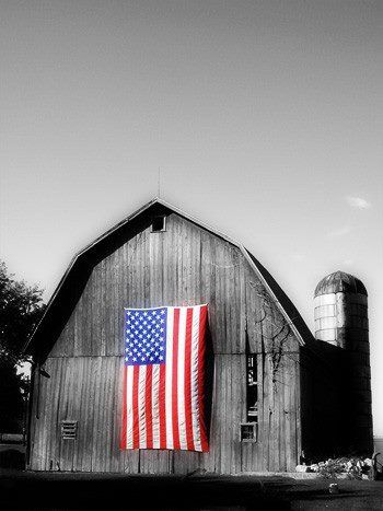 A Large American Flag Was Hung On An Old Barn Shortly