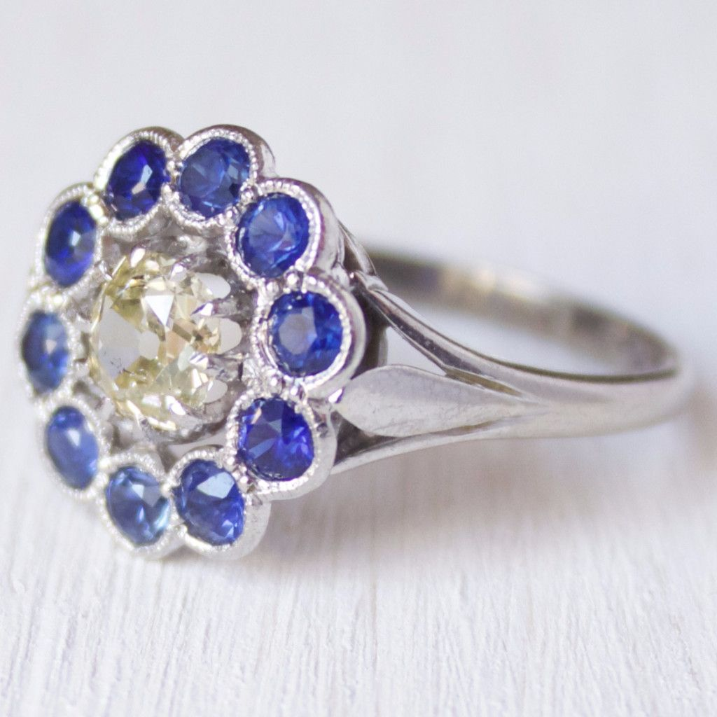 The Grace ring is a vintage Edwardian engagement ring centering a 0.55 carat old mine cut diamond surrounded by a halo of 10 round bezel set sapphires in a platinum mounting. The bezels are adorned wi