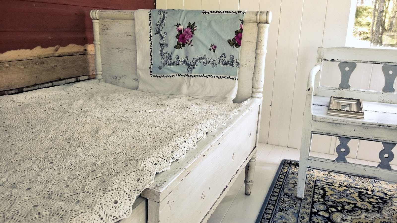 White wooden antique bed with lace cover. Raw, Scandinavian style.