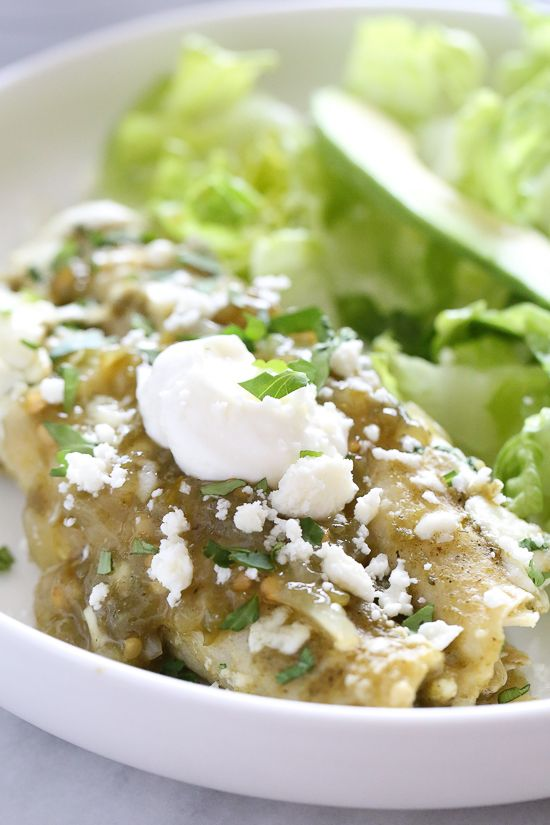 Traditional Mexican green chicken enchiladas, made lighter than the typical restaurant dish served throughout the US. Made with white corn tortillas, poached chicken breasts and a light coating of queso fresco, this dish is satisfying but won't weigh you down.