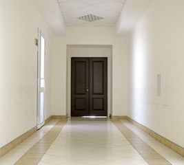 White hallway with marble floor and brown door in hospital
