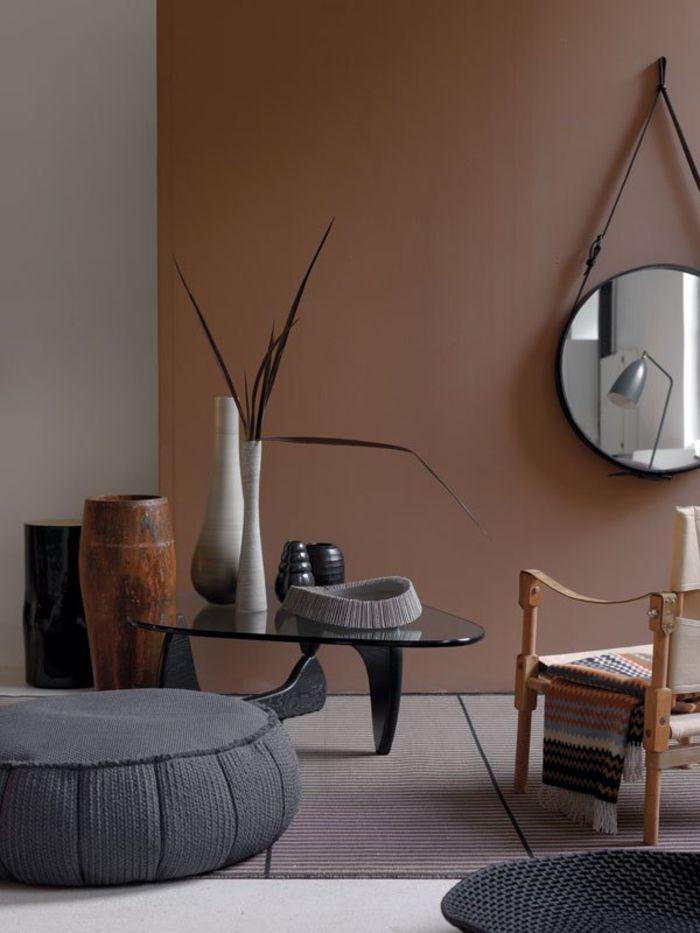 la palette des couleur du salon ethnique chic a inspiration africaine pouf gris associe a une table elegante en verre noire