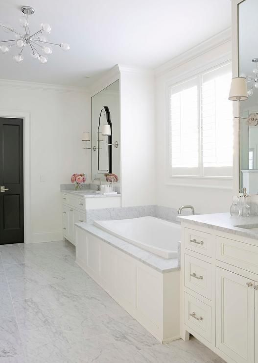 Sophisticated master bathroom features a wainscoted tub with marble deck placed under windows flanked by his and hers washstands topped with gray marble under framed mirrors layered with Allen + Roth Hovan Arch Frameless Mirrors lit by Thomas O'Brien Bryant Sconces.