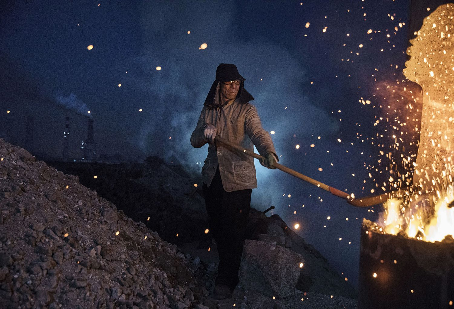 A Chinese laborer loads coal into a furnace as he works at an unauthorized steel factory in Inner Mongolia, on November 3, 2016.