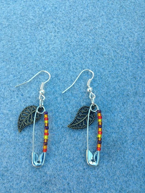 """Autumn leaves dangle earrings feature a safety pin adorned in traditional autumn colors and a leaf, creating a lovely Fall ambience. All proceeds benefit ProPublica.  https://www.propublica.org/  ProPublica is an independent, nonprofit newsroom that produces investigative journalism in the public interest. Our work focuses exclusively on truly important stories, stories with """"moral force."""" We do this by producing journalism that shines a light on exploitation of the weak by the..."""