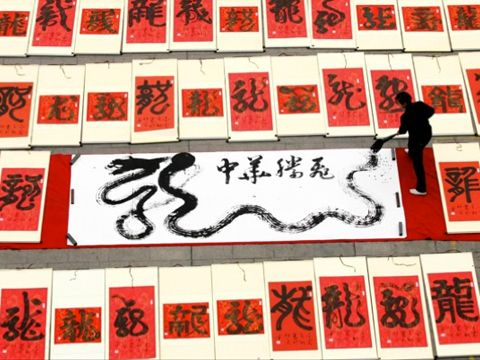 "A calligrapher writes various characters meaning ""dragon"" to commemorate this year's Chinese zodiac during lunar new year celebrations. Photo: Agence France-Presse"