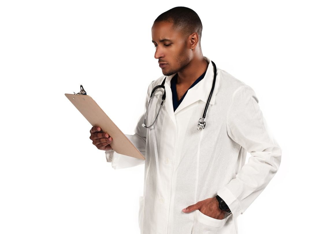 African american male doctor looking at a clipboard by