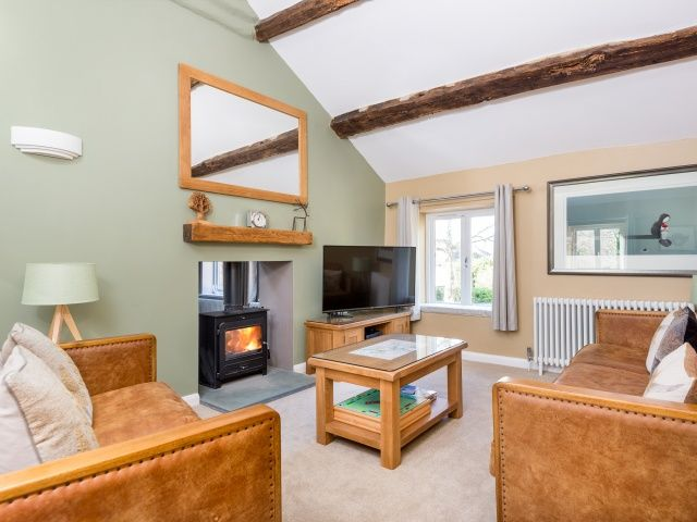 The Stables has fabulous, soft and comfortable furnishings. Relax in this light and spacious living room by the traditional wood burning stove.