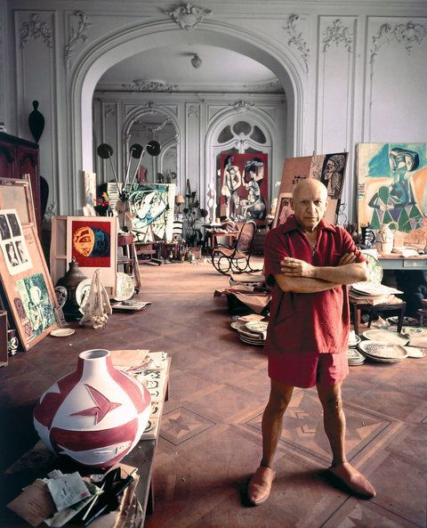 Pablo Picasso photographed in his studio near Cannes, France in 1956. The Thonet rocking chair in the distance appears in many of his paintings.