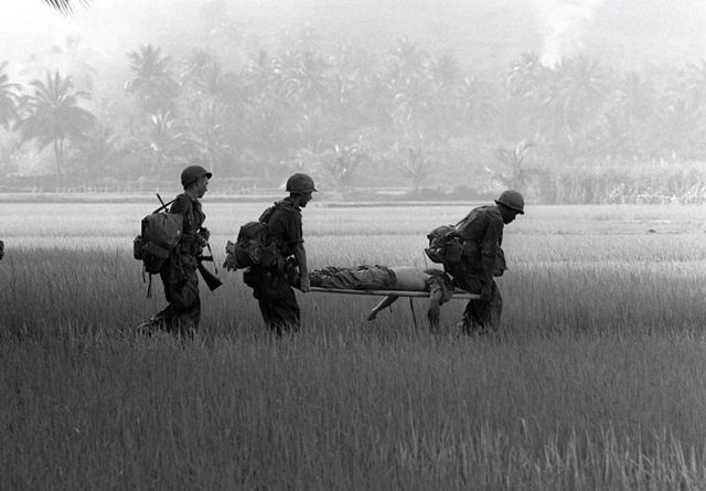 U.S. troops carry the body of a fellow soldier across a rice paddy for helicopter evacuation near Bong Son in early February 1966.
