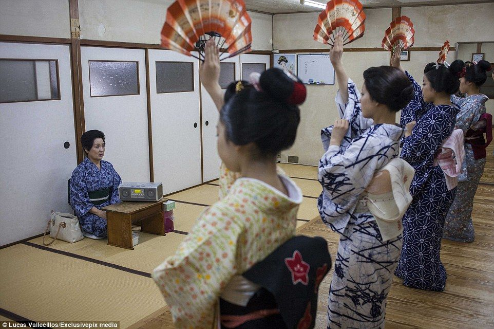 A Okasan (Japanese for mother) teaches protégés a traditional dance using fans