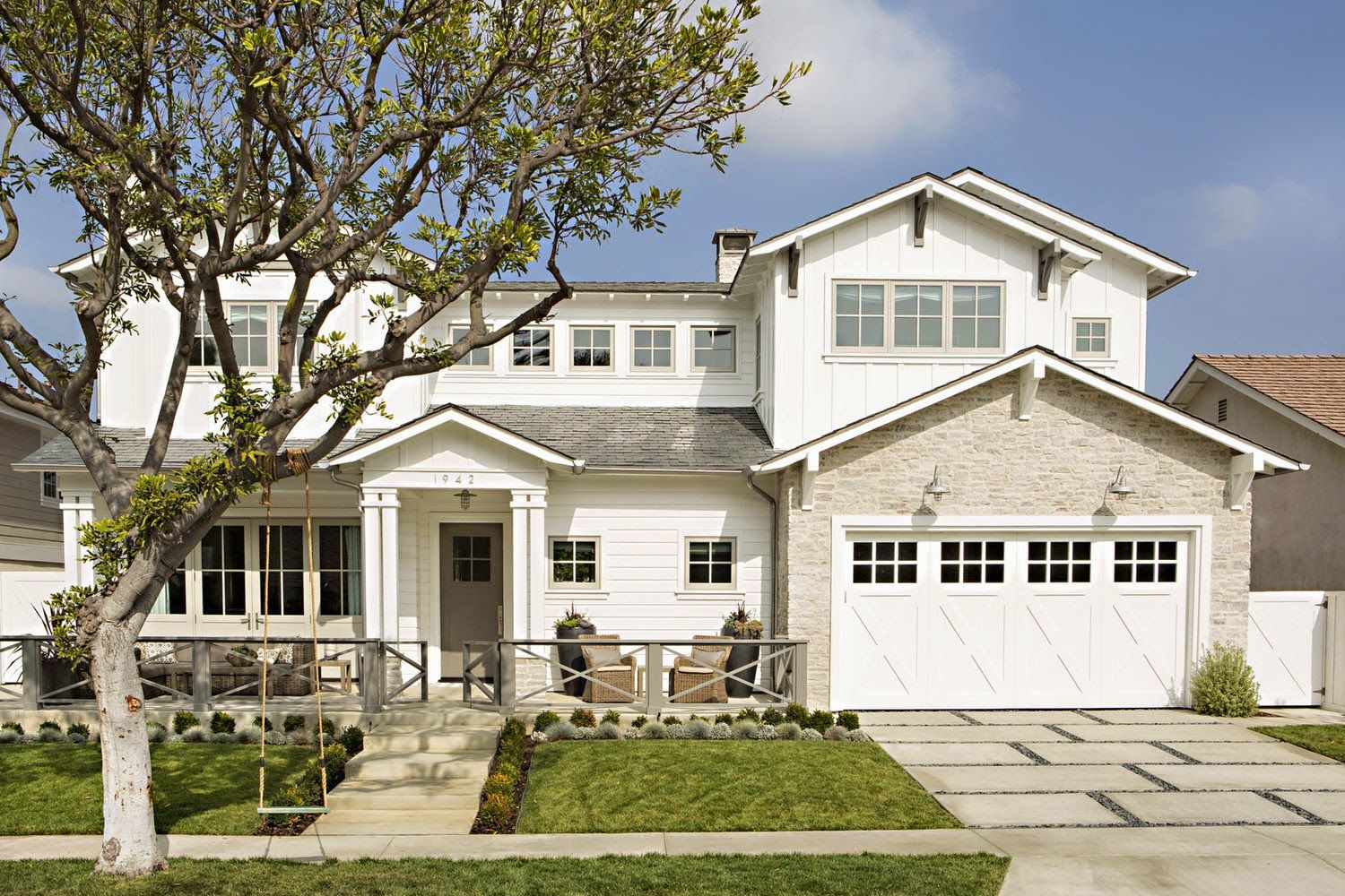Classic white and stone exterior with a barn style garage for Beach style house exterior