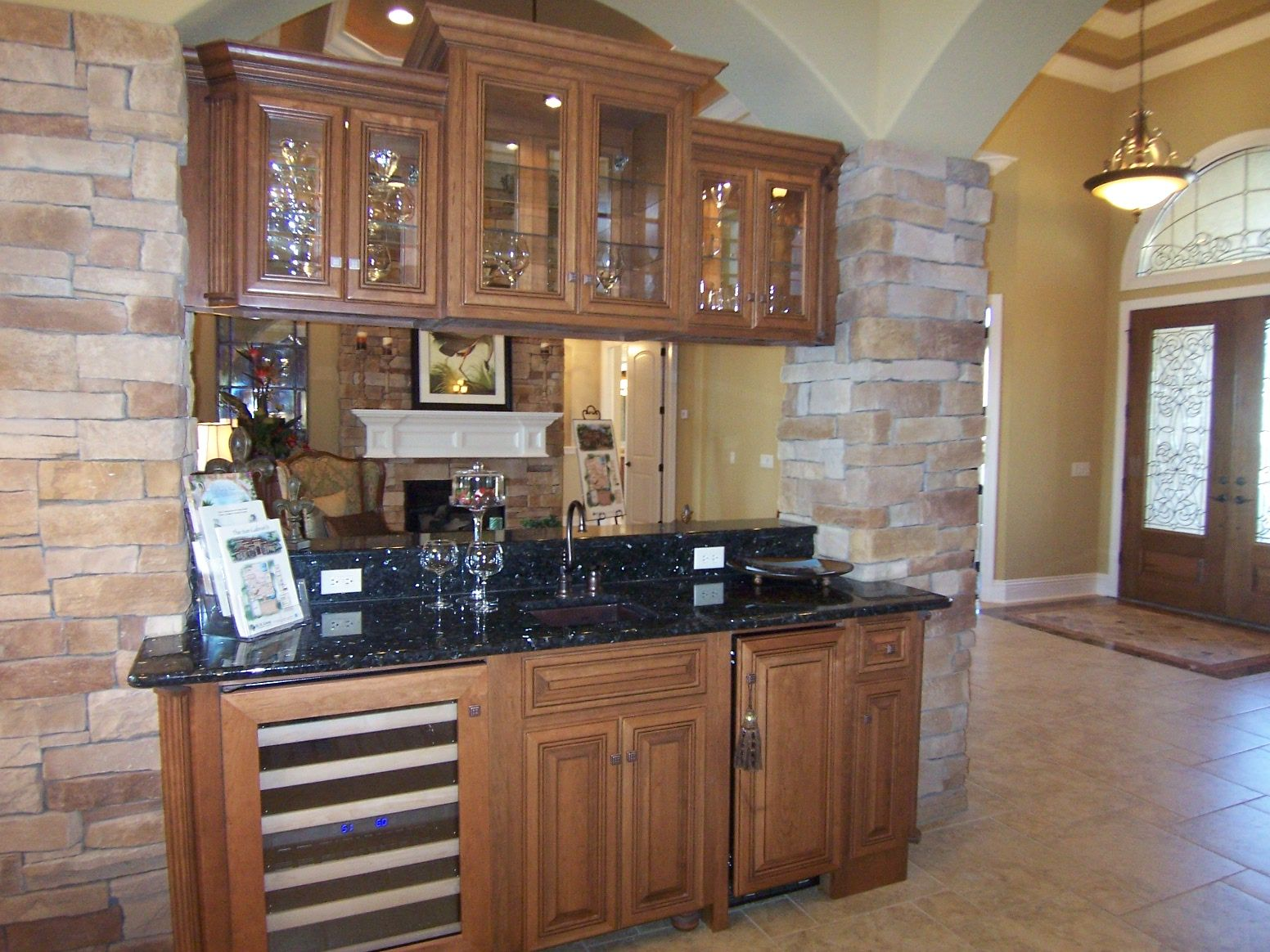 Hickory Cabinets With Doublesided Glass Doors Floating Between Stone Columns Make A Great Room Divider With Less Hickory Cabinets Kitchen Cabinets Great Rooms