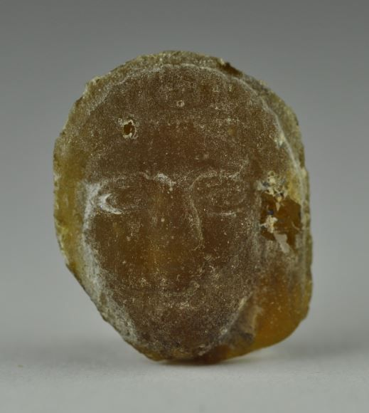 Roman gass token with two heads, 1st century B.C. Eastern Mediterranean, yellow glass with face of woman at each side, 1.8 cm high. Private collection