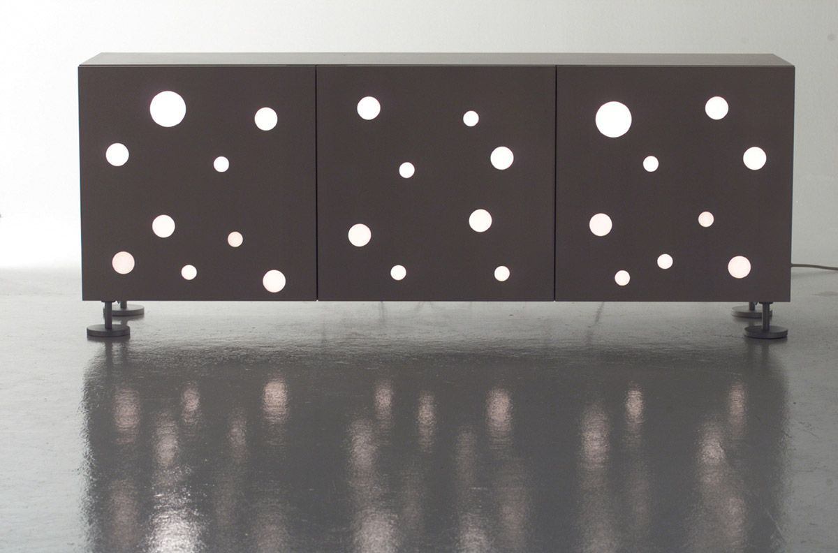 Design: Toyo Ito, 2003 Nel disegnare Polka Dots, Toyo Ito ha inserito sulle ante una serie disordinata di inserti circolari in metacrilato, in contrasto con la struttura minimale e rigorosa del mobile. Un pensiero grafico che rimanda al teatro Za-Koenji di Tokyo, anch'esso progettato dal grande architetto. Gli inserti rappresentano, come ci ricorda il nome …