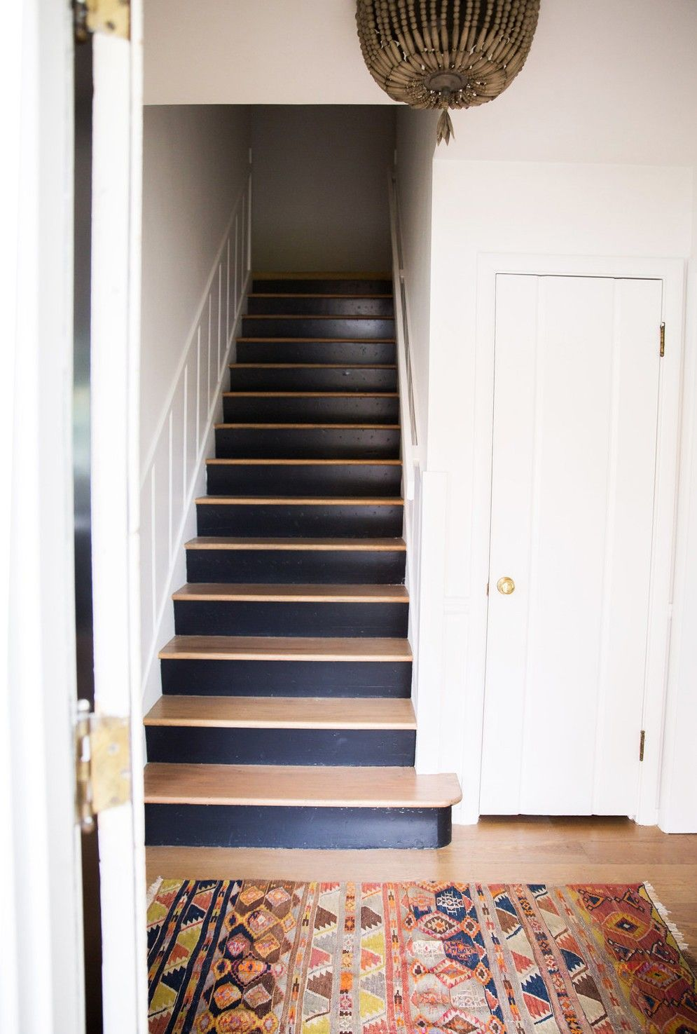 Twotoned wood stairs pair with wrought iron railing for