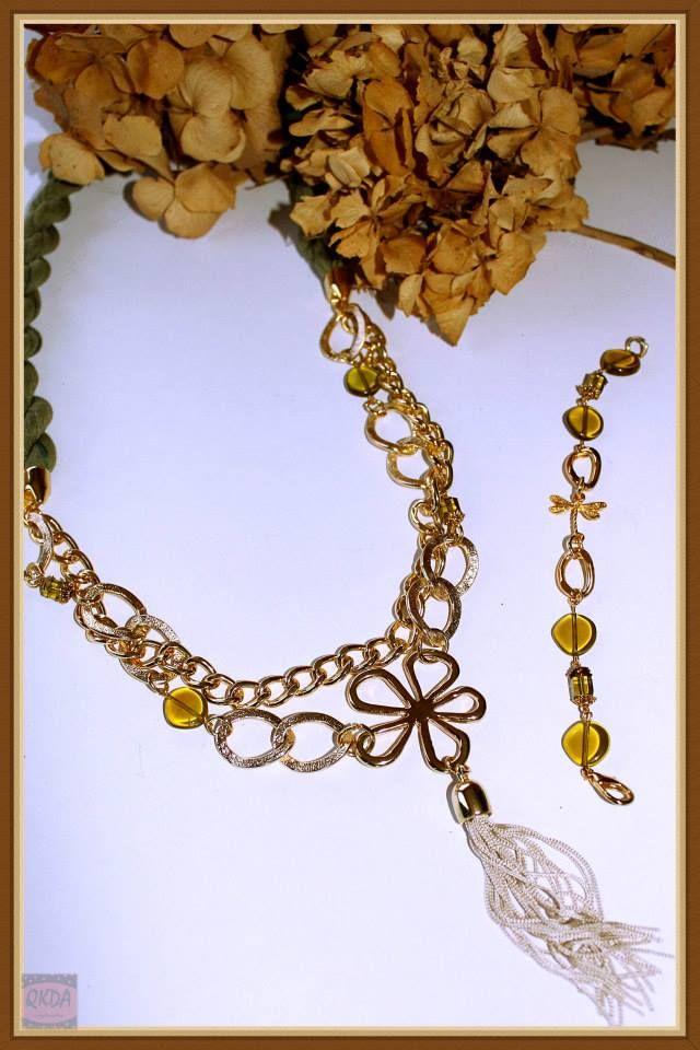 -Collar largo tonos verdes, cadena dorada , entrepieza flor bañada en oro y borlón beige-Pulsera piedras cristal verde y dorada con entrepieza libelula