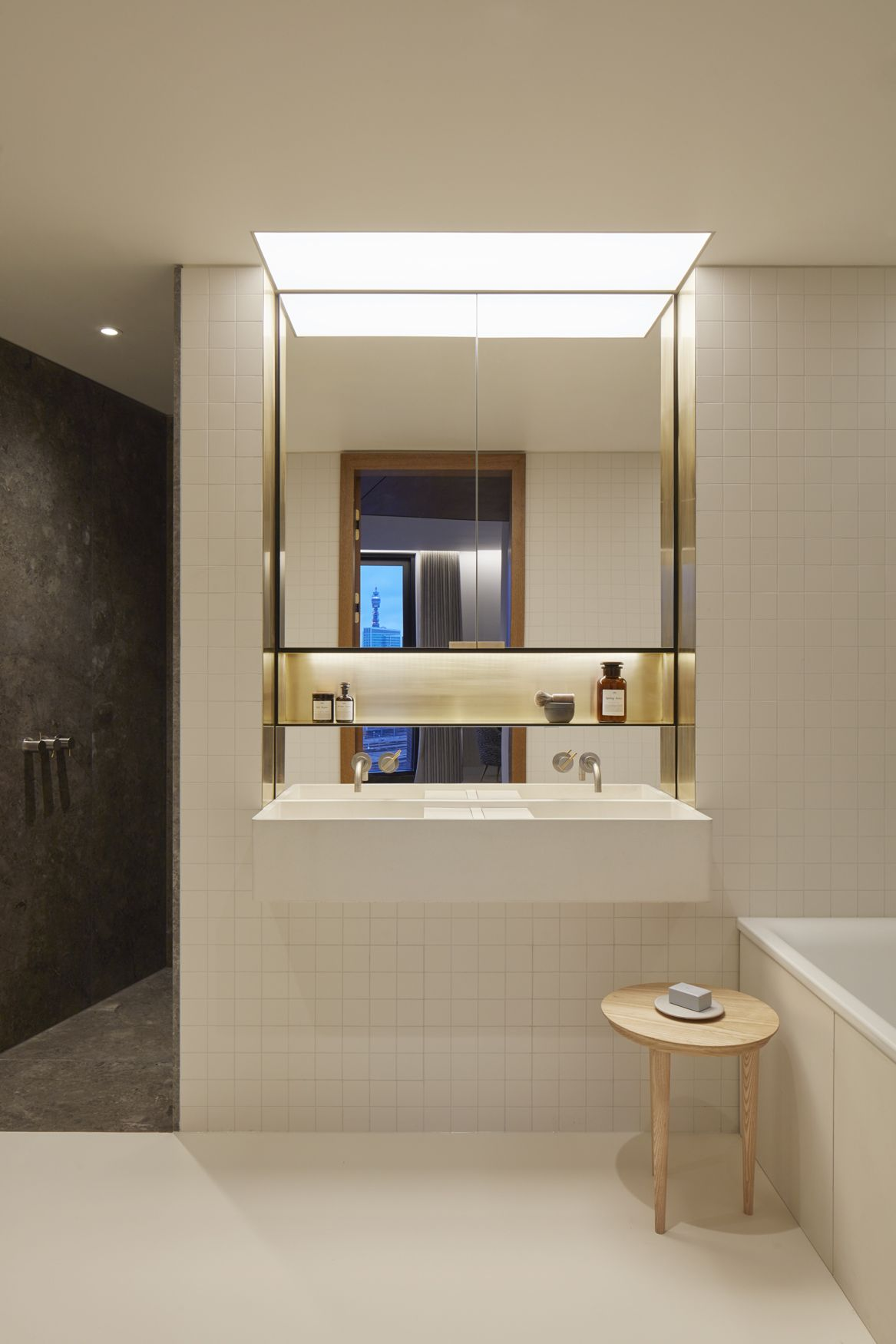 A material palette of engineered board brushed stainless steel and brass is applied throughout the