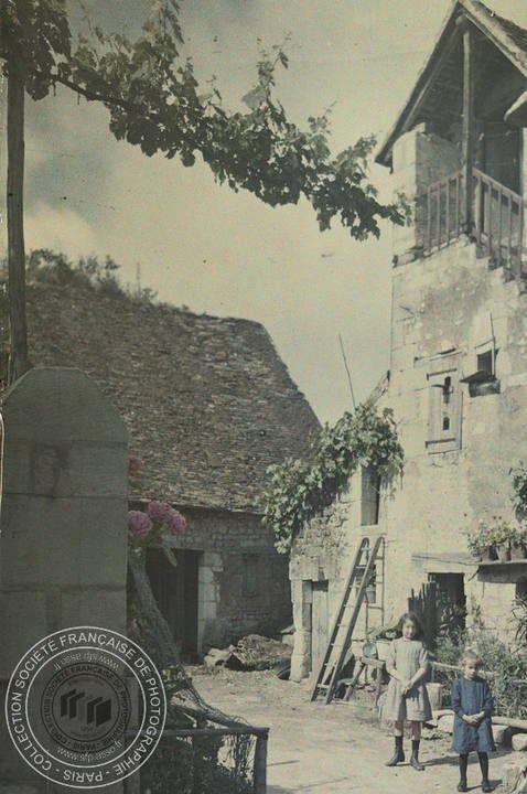 [Deux enfants dans la cour d'une ferme], Charles ADRIEN, entre 1907 et 1930. - 1 photographie positive transparente: verre autochrome, couleur; 9 x 12 cm