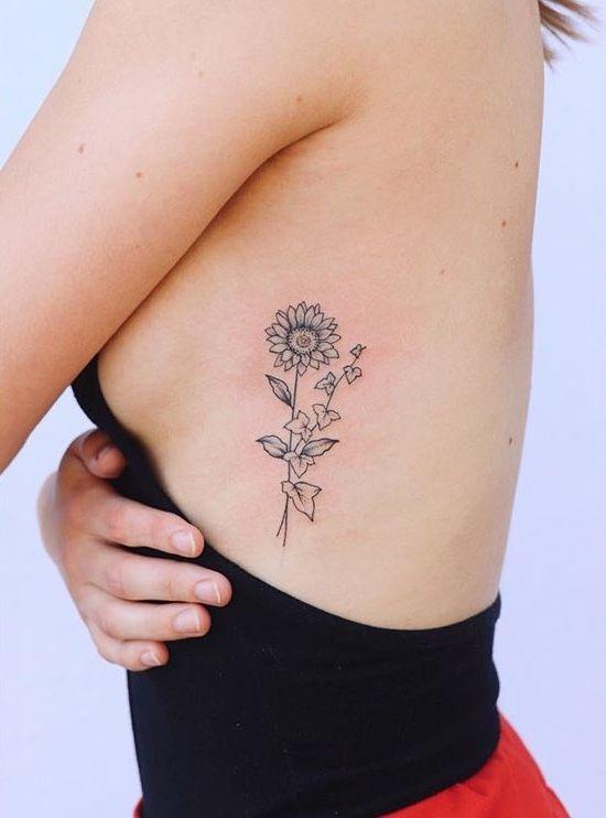 Sunflower and ivy rib tattoo
