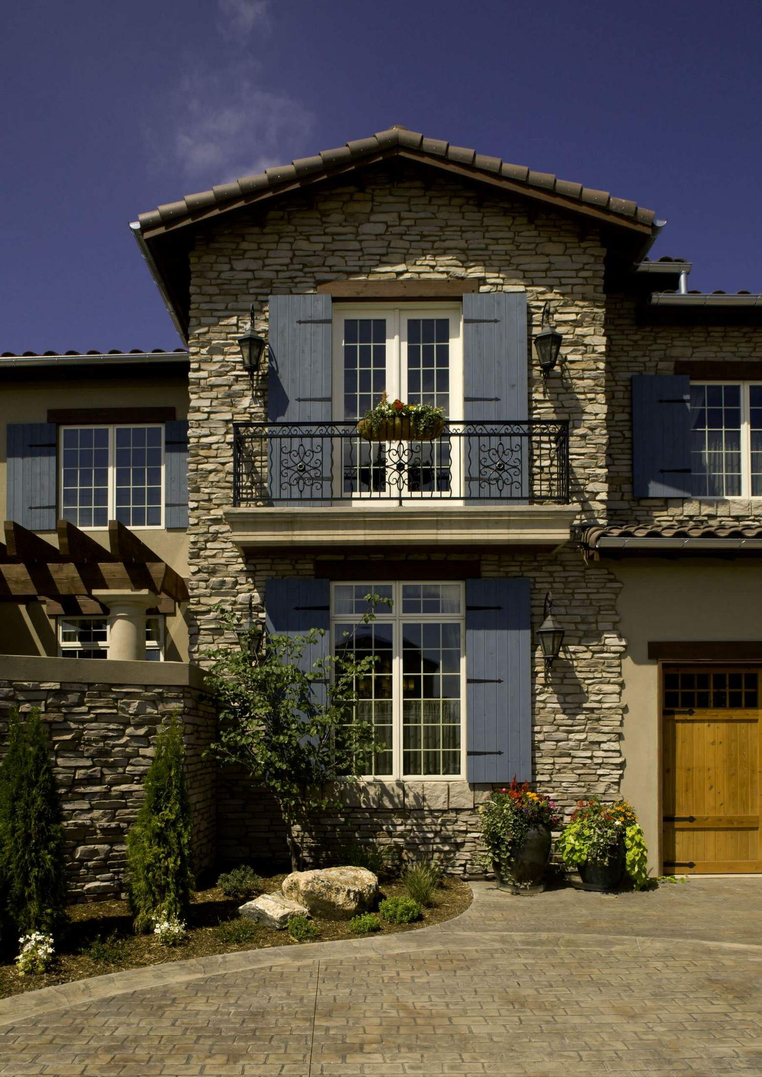Mediterranean style stone facade with blue window shutters gas
