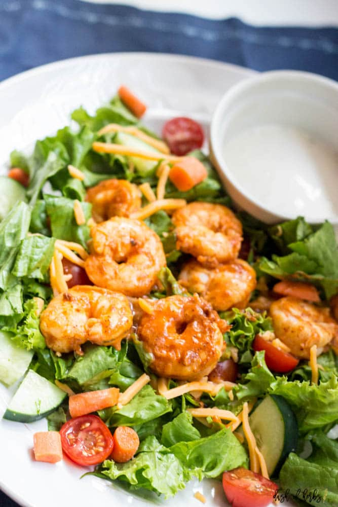 A close up image of the Buffalo Shrimp Salad recipe shown on a white plate. You can see the buffalo shrimp, tomatoes, lettuce, cucumbers and cheese. There is a small white bowl of ranch on the plate as well. #buffaloshrimp A close up image of the Buffalo Shrimp Salad recipe shown on a white plate. You can see the buffalo shrimp, tomatoes, lettuce, cucumbers and cheese. There is a small white bowl of ranch on the plate as well. #buffaloshrimp A close up image of the Buffalo Shrimp Salad recipe sh #buffaloshrimp