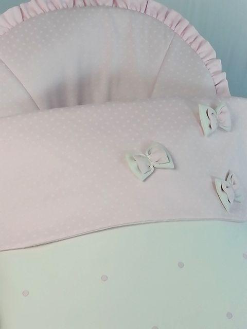 Detalle babero saco en polipiel con babero y funda en jacquard topos rosa con lazos