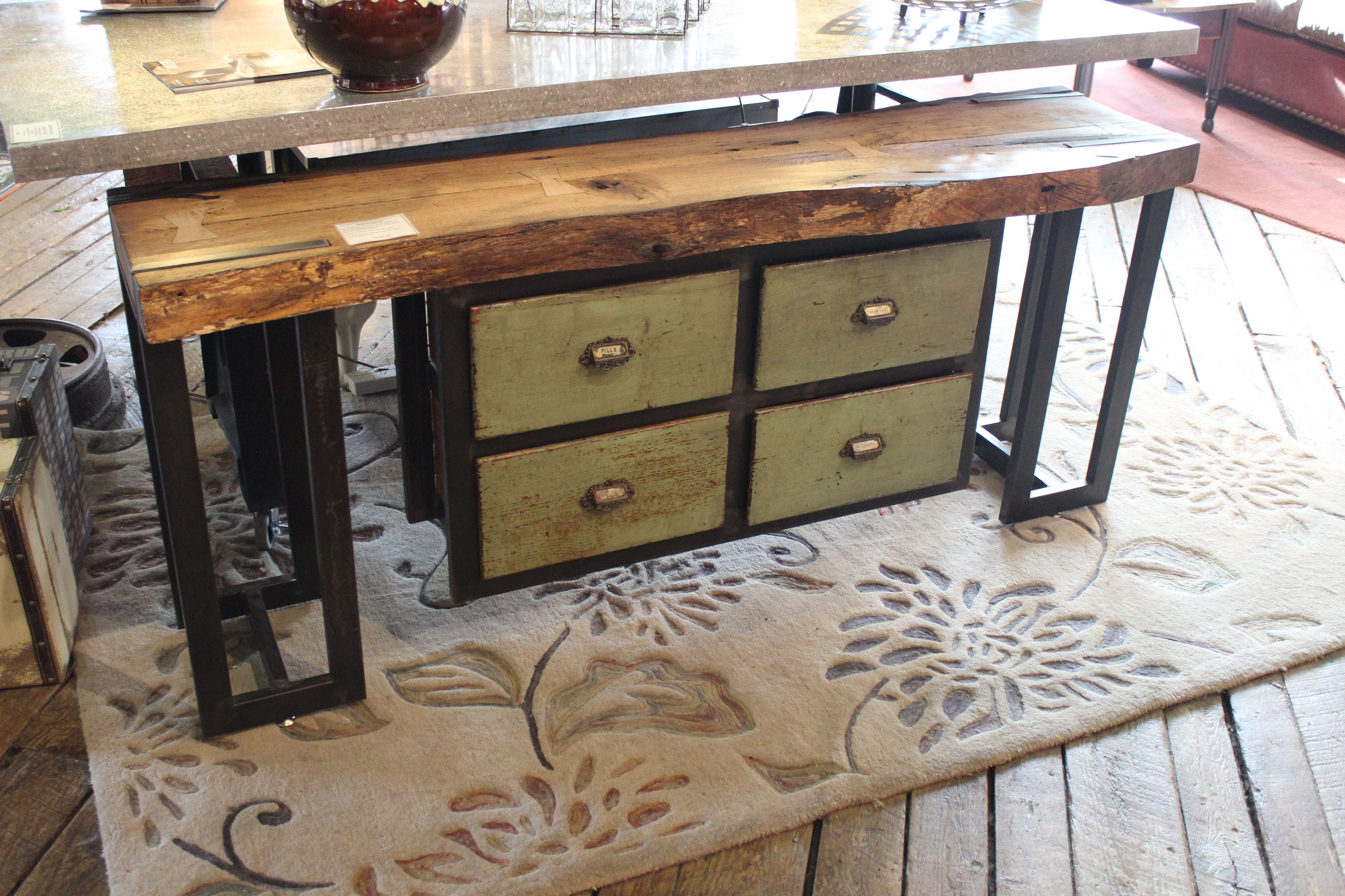 sofa table made from live edge oak with butterfly joints, custom welded legs, and reclaimed vintage apothecary drawers in a custom metal frame.