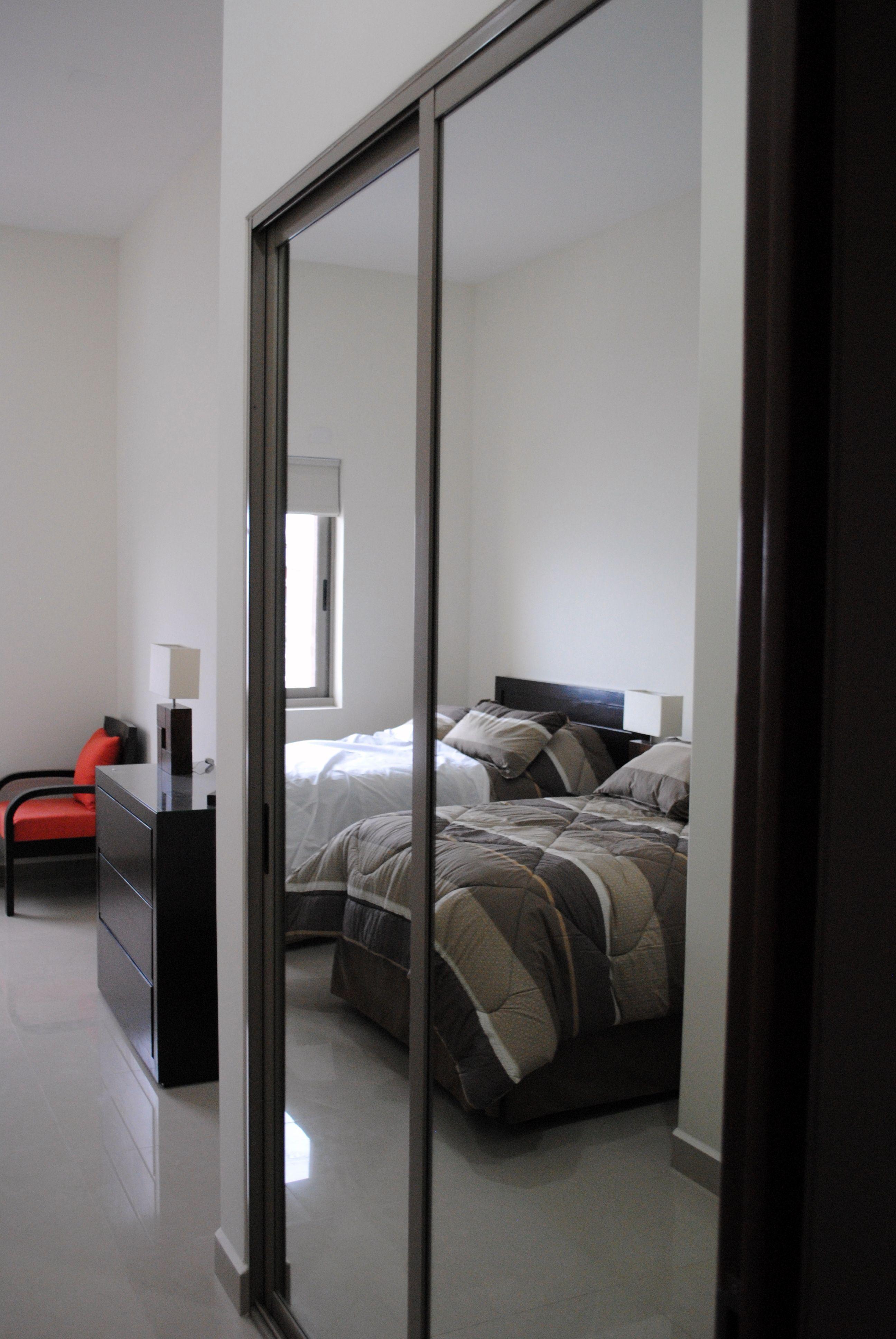 Closet con puerta corrediza de espejo vestidores for Puertas corredizas