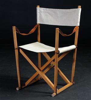 Mogens Koch 1898-1992. Foldestol med stel af bøgetræ, sæde og ryg af lyst kanvas, armstropper af patineret kernelæder.  Formgivet i 1932. Fremstillet hos Cado, model MK16, messingplaketter herfra. Fremstår med brugsspor.