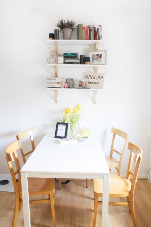 Die Einrichtung Ist Simpel Gehalten: Ein Regal Mit Bewusst Platzierten Deko Elementen,  Farbige Stühle, Die Sich Vom Tisch Abheben Und Ein Ansonsten Cleaner ...
