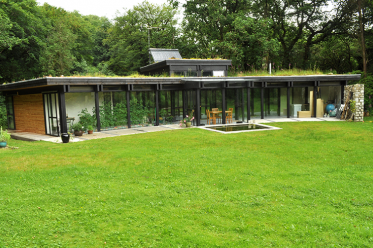 The single-storey house is topped with a green roof