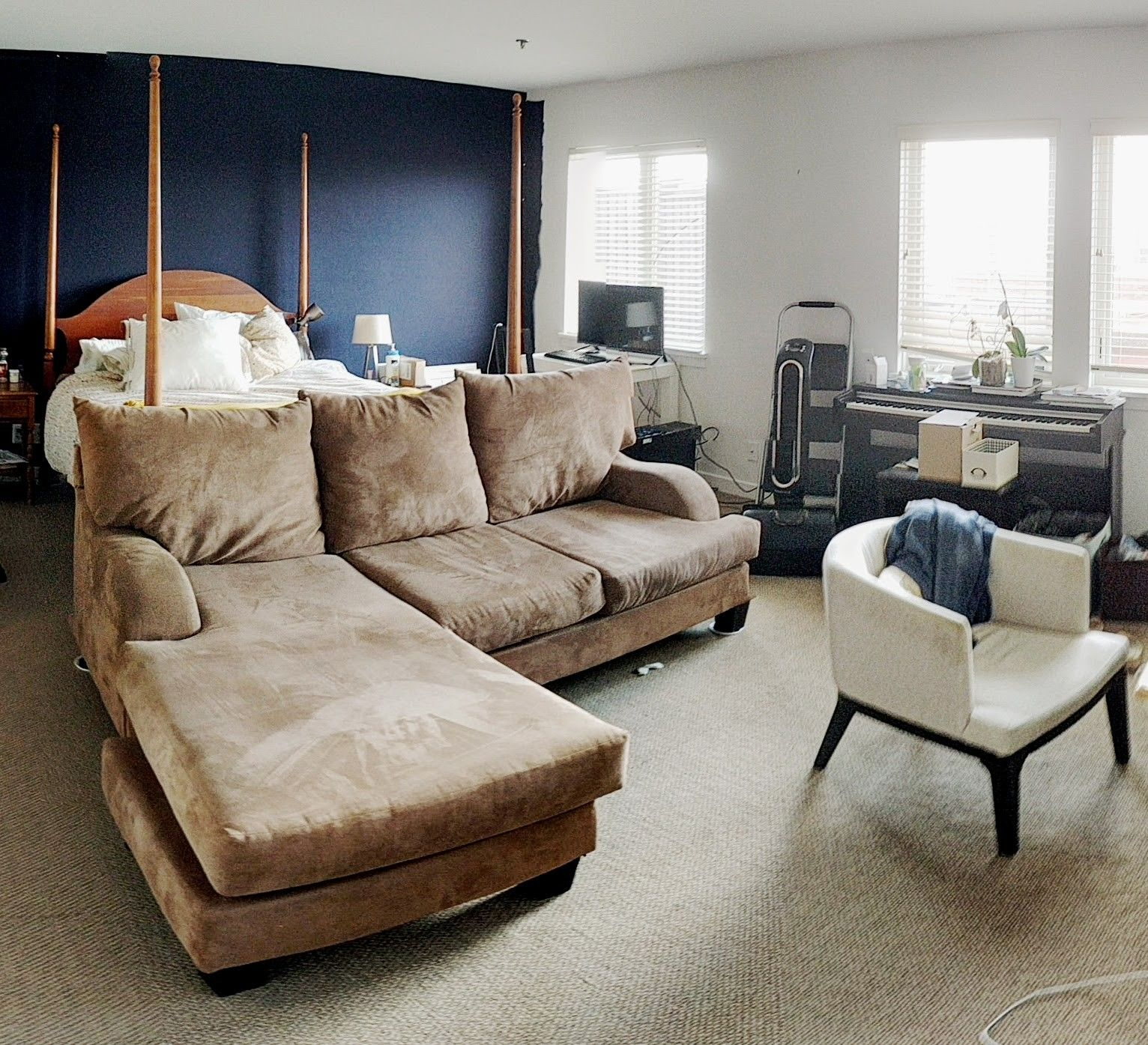 Put your sofa at foot of bed in the main room. So your bed