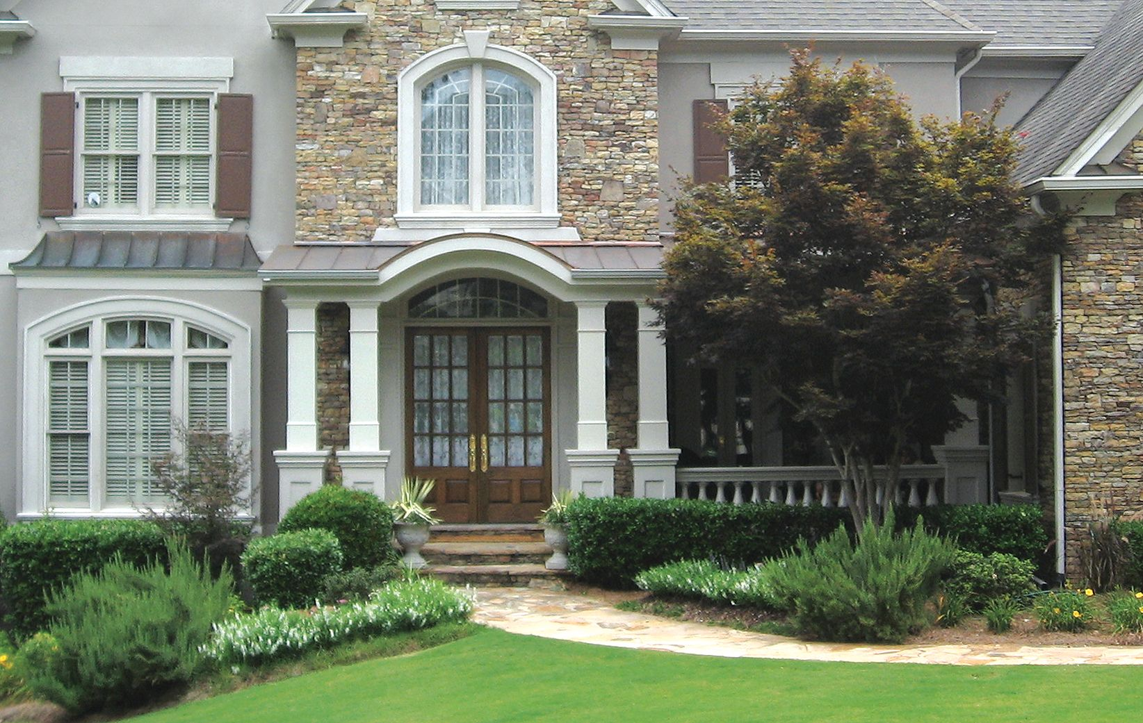 Front Porch With Arched Entry Metal Roof And Stone Piers