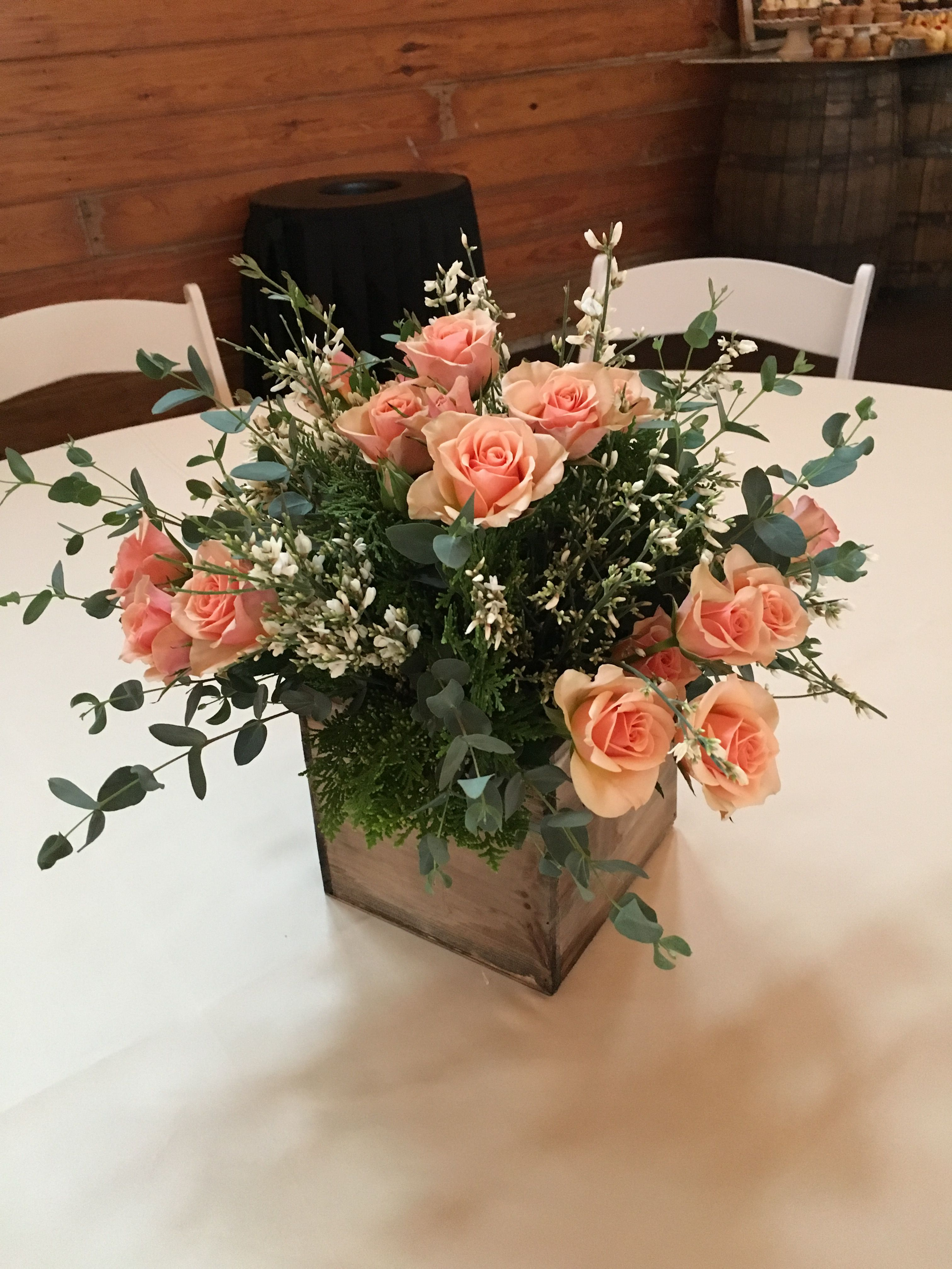 A wooden square vessel creates a great short wedding centerpiece ...